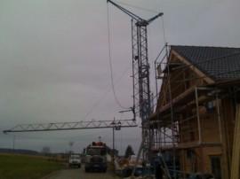 Baukran am Blockhaus für Dacheindeckung mit Gerüst