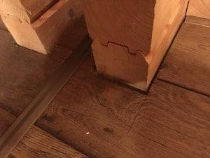 Lücke zwischen Holzdielen und Blockbohlen im Blockhaus