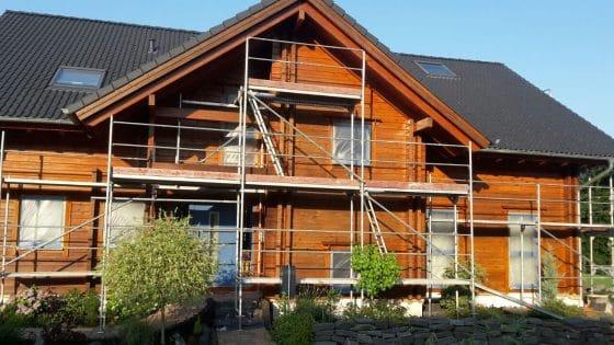 Blockhaus mit Gerüst für Anstrich